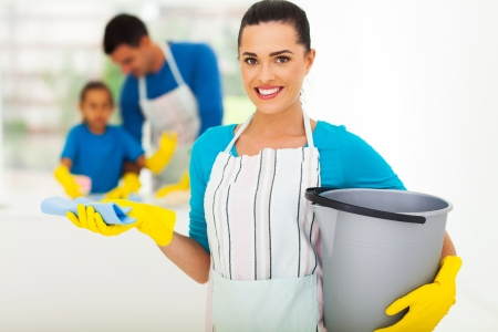 beautiful young woman with cleaning tools in front of family photo