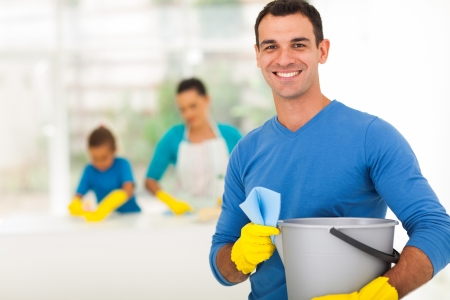 clean kitchen: happy family man cleaning home with his family Stock Photo