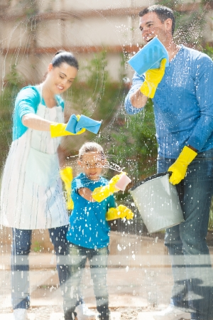 happy young family cleaning home window glass