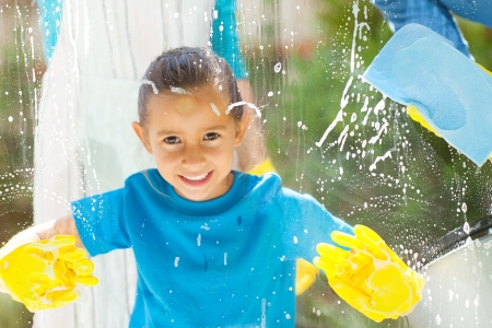 cute little girl cleaning window glass with parents at home photo