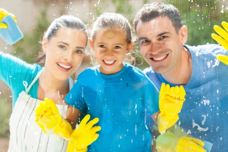 happy young family of three cleaning home window glass together photo