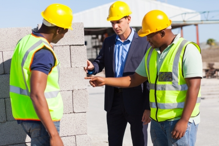 skilled labour: construction workers with their manager checking bricks quality Stock Photo