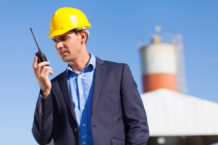 handsome construction manager using walkie talkie outdoors photo