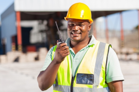 african male builder talking on his radio photo