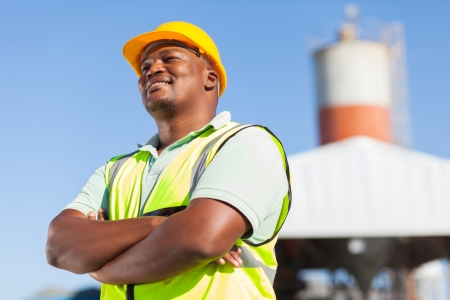 blue helmet: happy african male constructor with arms folded Stock Photo