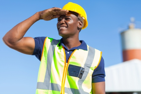 builder construction: smiling african builder looking into distance