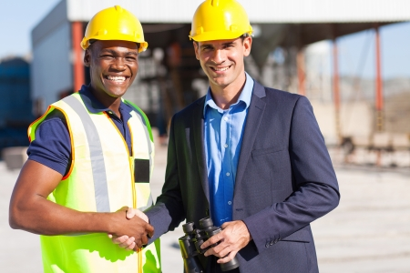 site manager: cheerful industrial manager and worker outdoors