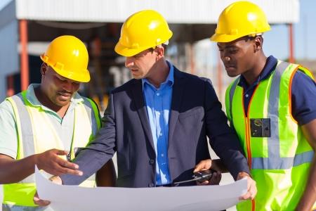 建設現場での男性の建築家および建設労働者のグループ