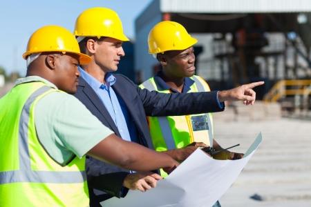 arquitecto: grupo de arquitectos y trabajadores de la construcción en el sitio con el proyecto original