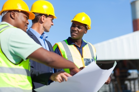 industrial worker: group of professional construction workers and architect on site