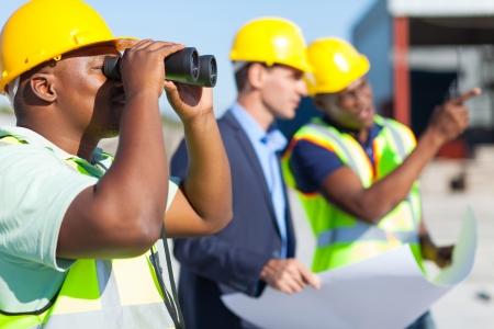 Travailleur de la construction africain à l'aide des jumelles regardant chantier Banque d'images - 20022614