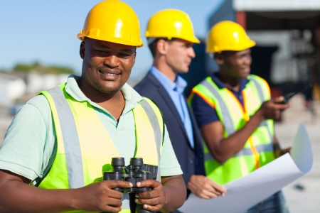 african construction worker holding binoculars standing with colleagues  photo