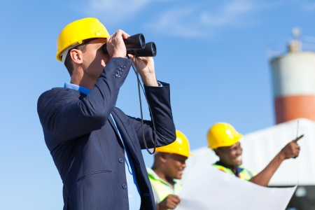 architect using binoculars looking at construction site with construction workers photo