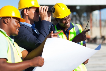 walkie: project manager using binoculars looking at the construction site with workers