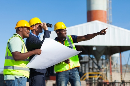 foreman: project manager visiting construction site with construction workers Stock Photo