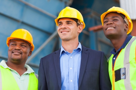 blue collar: optimistic heavy industry manager and workers portrait
