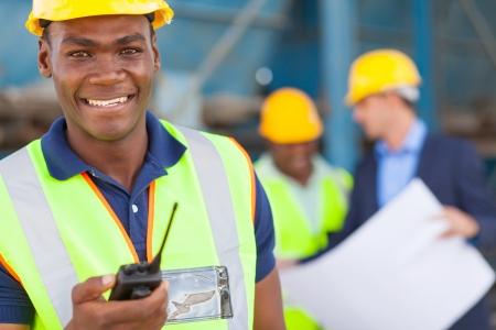 obreros trabajando: feliz trabajador industrial afroamericano con walkie talkie en sitio con los colegas