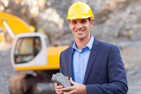 mining machinery: happy manager in mining site holding ore Stock Photo