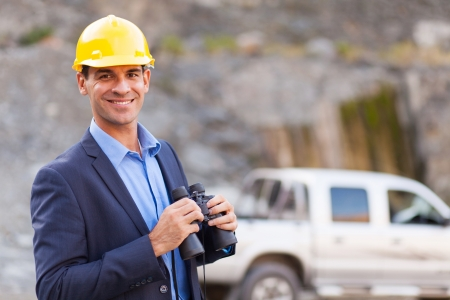 portrait of smiling mine manager with binoculars visiting mining site photo