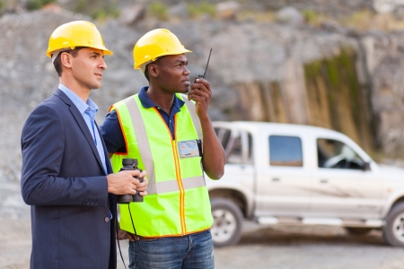 mining: mine manager and worker visiting mining site