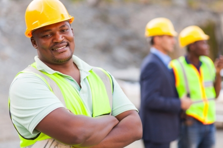 ppe: smiling african mine worker at mining site with colleagues