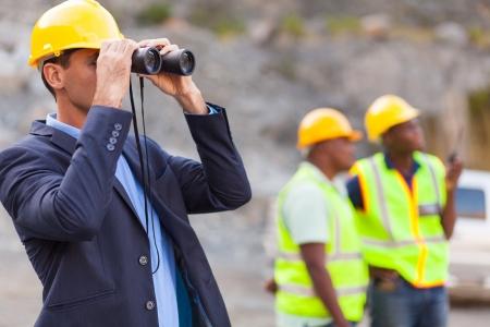mijnbouw: mijne manager met een verrekijker op mijnsite Stockfoto