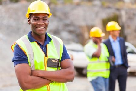 feliz trabajador industrial africano con los brazos cruzados
