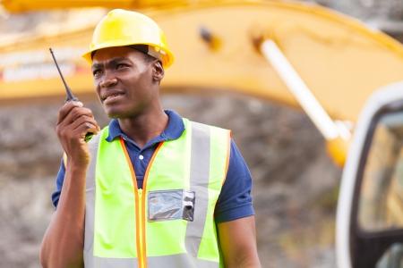 african american trabajador de la mina con walkie-talkie en la mina