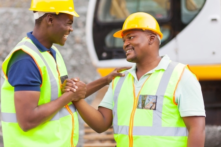 mining equipment: cheerful african mine workers hands together to form brotherhood Stock Photo