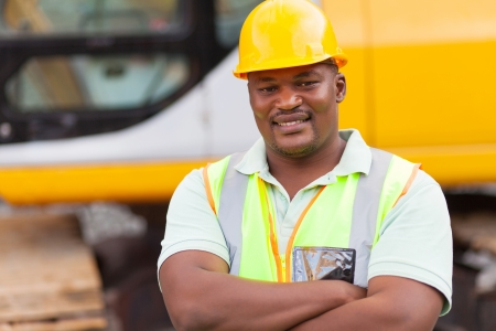 ppe: smiling african mine worker with arms folded at mining site