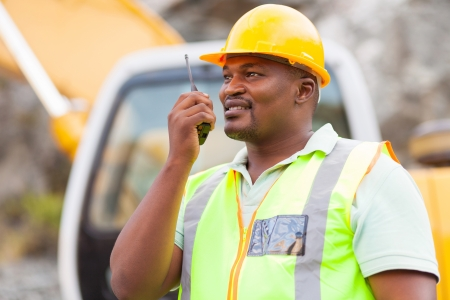 ppe: afro american industrial worker talking on walkie-talkie at mining site Stock Photo