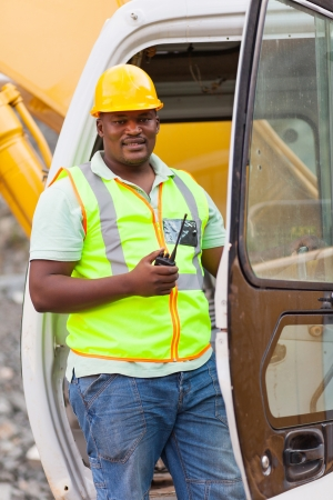 road worker: african road construction worker on bulldozer and holding a walkie talkie