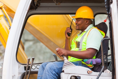 construction machines: african industrial worker operating bulldozer while talking on walkie-talkie Stock Photo
