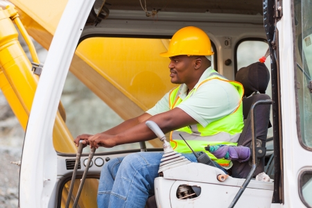 heavy equipment: african american man operates excavator on building site Stock Photo