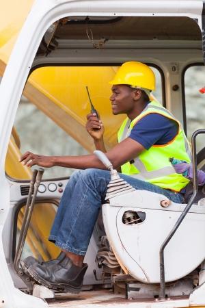 afro american: afro american man operates excavator while using walkie-talkie