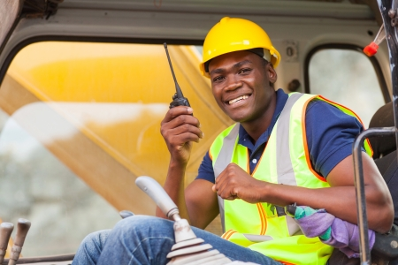 job site: cheerful african bulldozer operator talking on walkie talkie on construction site