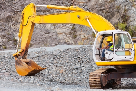 quarries: african road construction worker operating excavator on construction site Stock Photo