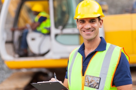 construction helmet: handsome road construction supervisor with clipboard Stock Photo