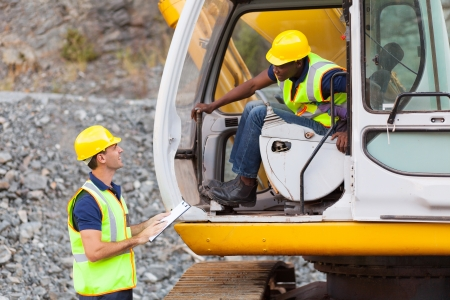 industrial site: cheerful construction foreman talking to excavator operator Stock Photo