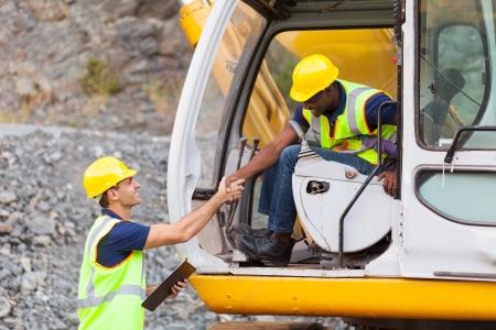 saludo de manos: gerente de construcci�n feliz apret�n de manos con el operador de excavadora en el sitio de construcci�n Foto de archivo