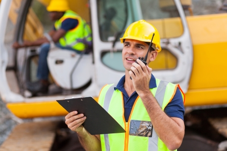 construction site: construction foreman talking on walkie-talkie holding clipboard