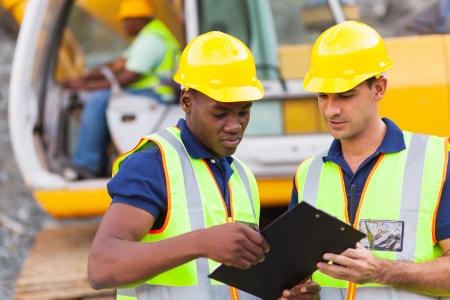 ouvrier: construction collègues de discuter sur le site de construction du plan de travail