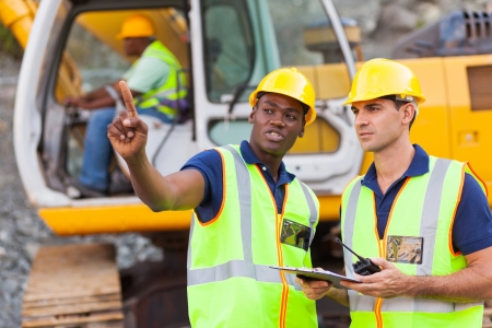 road worker: co-workers talking at construction site with bulldozer behind them Stock Photo