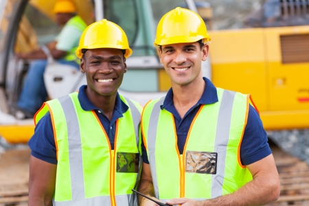 building worker: two cheerful male road construction workers on construction site Stock Photo