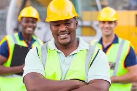 同僚とアフリカの建設労働者の笑みを浮かべてください。