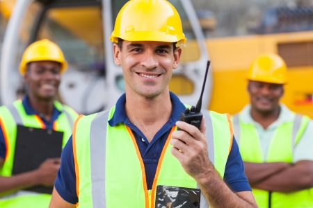 safety vest: portrait of smiling contractor with walkie-talkie