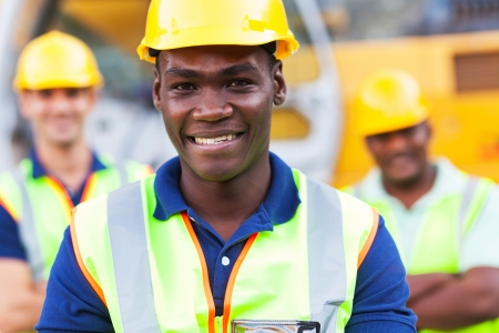 happy african american construction worker in front of colleagues
