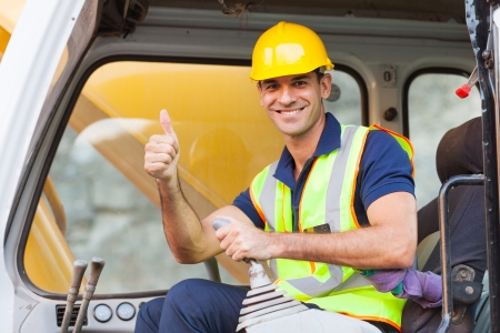 earthmover operator giving thumb up on construction site Stock Photo