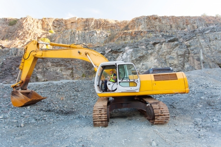 mine worker operating excavator on mining site photo