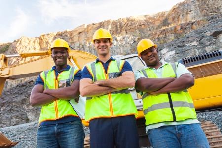 掘削機の横に腕を組んで立って採石場の労働者のグループ